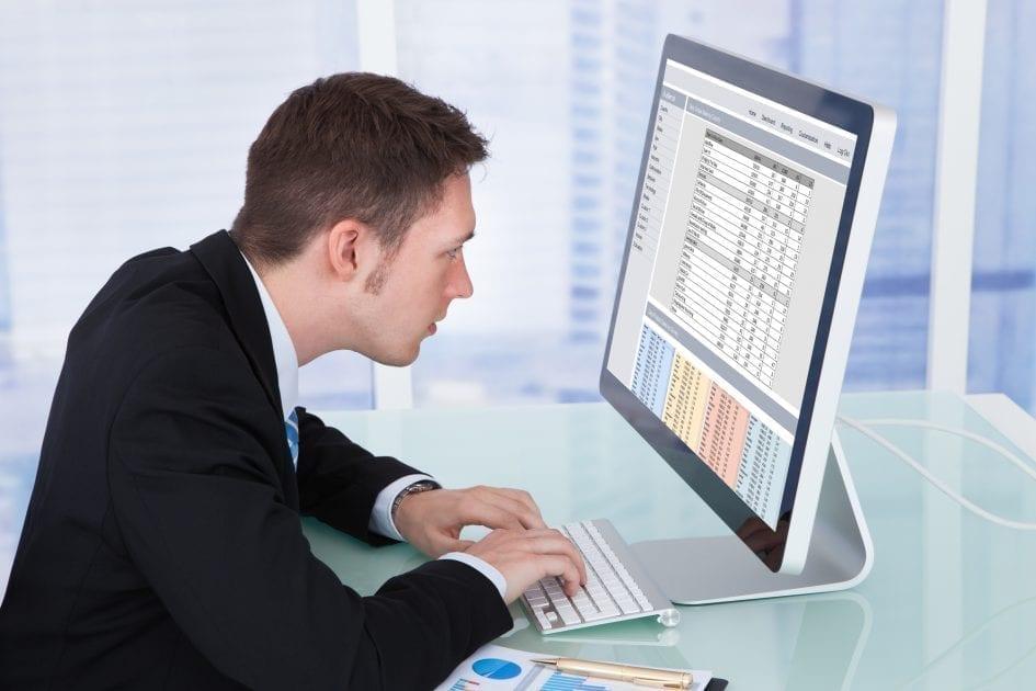 Konsentrert mann foran datamaskinen med anspent nakke og dårlig kroppsholdning